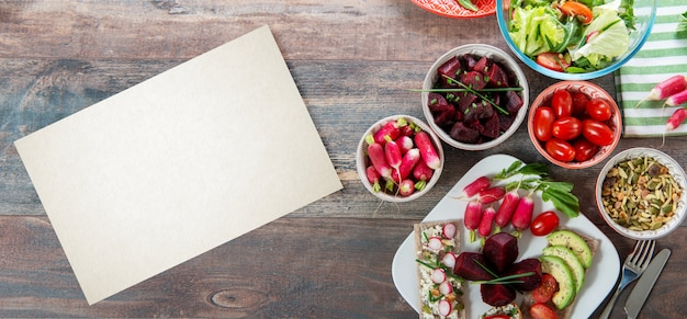 Ciotole e piatto di sana insalata vegana. varie verdure avocado, cetrioli, ravanelli
