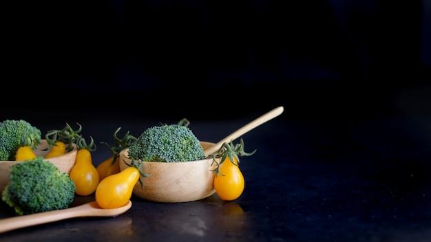 Ciotole in legno con broccoli e frutta