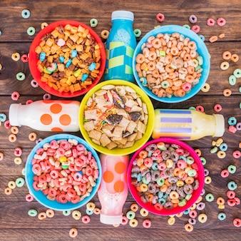 Ciotole luminose di cereali con bottiglie di latte sul tavolo