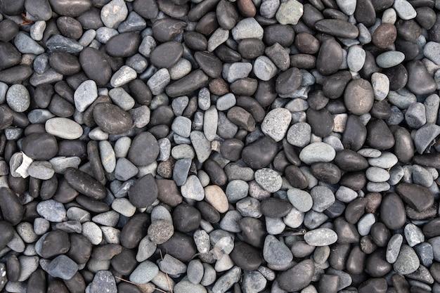 Ciottoli bianchi e neri per lo sfondo e la consistenza. il ciottolo di pietra o roccia è un segno di spa e religione zen.