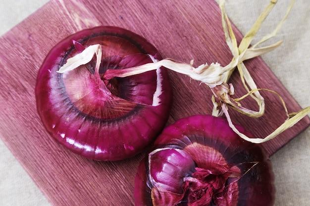 Cipolla dolce della crimea sul bordo di legno. grandi cipolle intere cipolle rosse per insalate