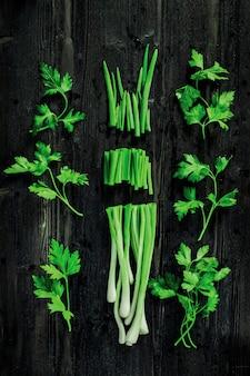 Cipolla e prezzemolo verdi freschi di taglio sullo scrittorio nero