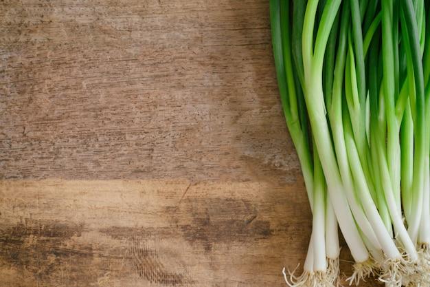 Cipolla fresca primavera o scalogno sulla tavola di legno