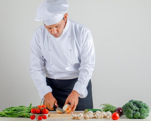 Cipolla maschio di taglio del cuoco unico sul bordo di legno in uniforme, grembiule e cappello in cucina