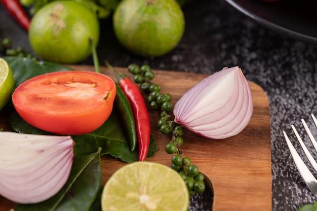 Cipolla, peperoncino, pepe fresco foglie di lime kaffir e lime adagiate su un tagliere di legno.