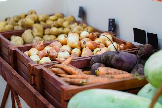Cipolle, carote, patate e barbabietole in scatole su uno scaffale in un negozio di verdure
