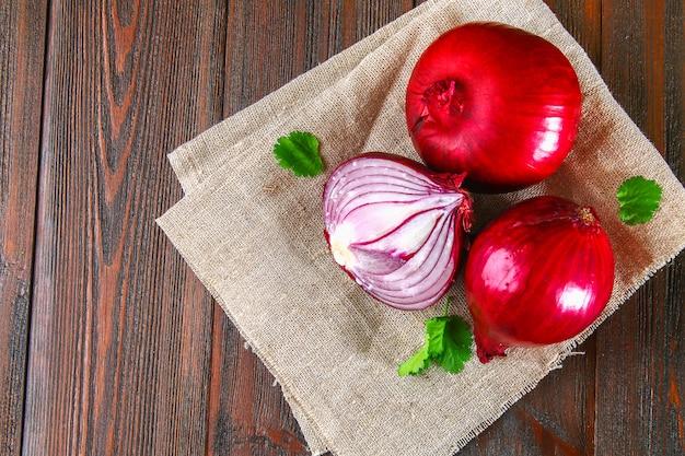 Cipolle rosse fresche e fette tritate su un tavolo di legno. vista dall'alto.