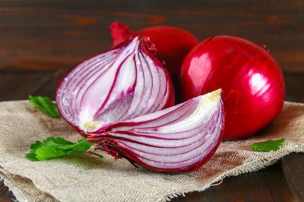 Cipolle rosse fresche e fette tritate su un tavolo di legno.
