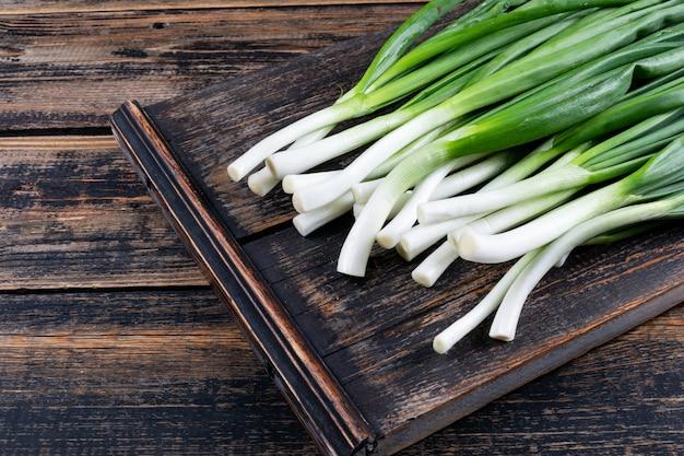 Cipollotti verdi o scalogno su un tagliere su un tavolo di legno scuro