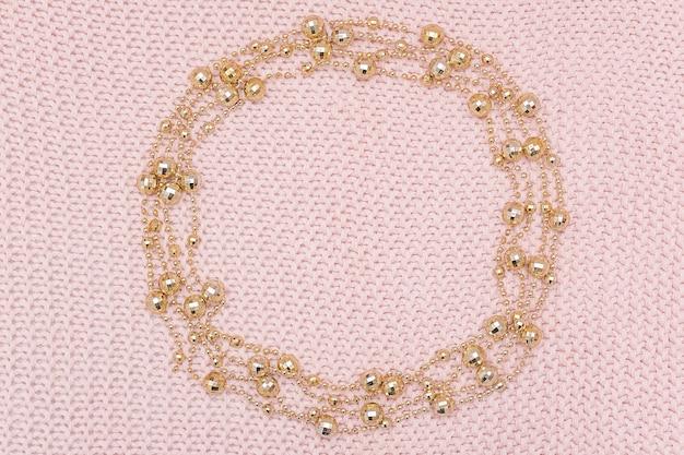 Circondi la struttura dalla ghirlanda dorata delle perle su fondo rosa tricottato.