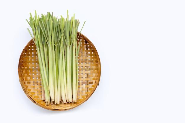 Citronella fresca sul canestro di trebbiatura di bambù di legno su fondo bianco.