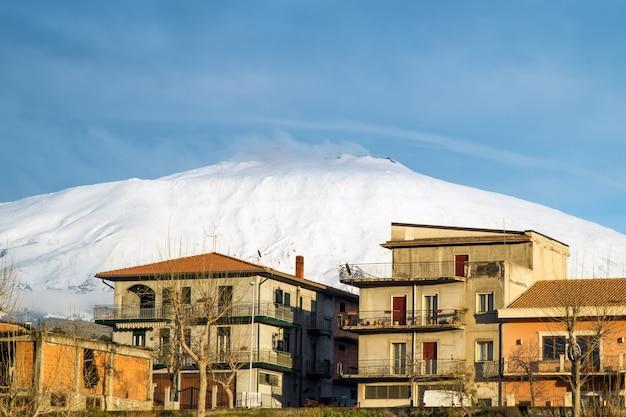 Città di bronte sotto il vulcano innevato e maestoso dell'etna
