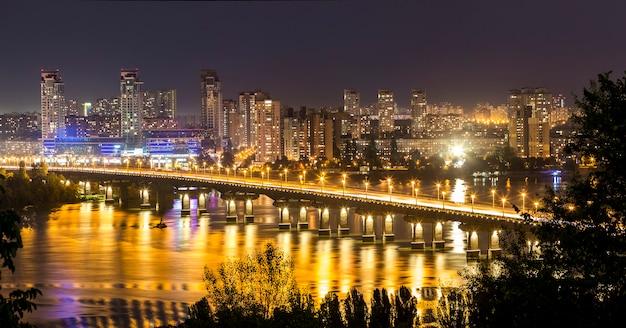Città di kiev (kiev), la capitale dell'ucraina di notte accanto al fiume dnipro (dniepr) con riflesso nell'acqua
