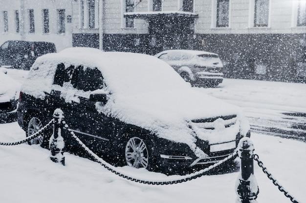 Città paralizzata durante forti nevicate. auto coperte di neve. ciclone potente durante l'inverno