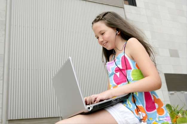 Città teenager bella del computer portatile della bambina del brunette
