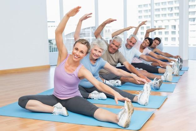 Classe che allunga le mani alla lezione di yoga