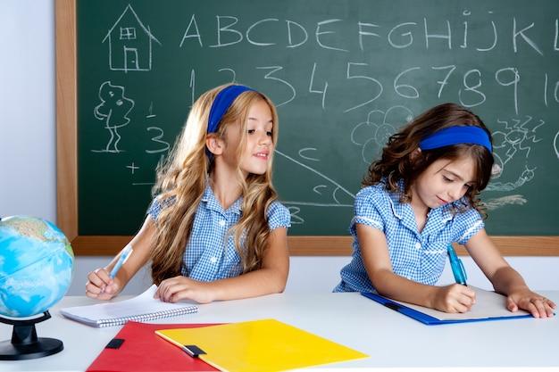 Classe con due studenti bambini che tradiscono il test