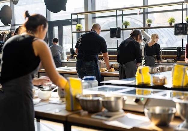 Classe culinaria vista posteriore del processo di cottura. diverse persone irriconoscibili in grembiule grigio in cucina imparano a cucinare. laboratorio di cucina. cucinare formazione