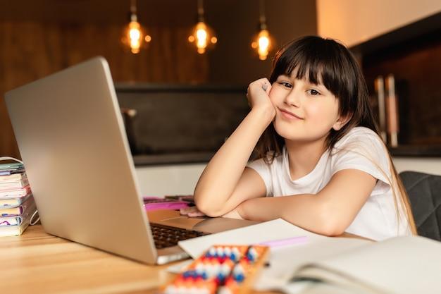 Classe di apprendimento online, studio online con insegnante di videochiamata, ragazza felice che impara online a casa