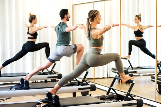 Classe in una palestra facendo pilates in piedi affondo