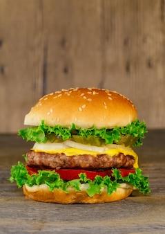 Classico cheeseburger deluxe con lattuga, cipolle, pomodori e sottaceti