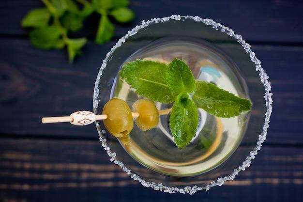 Classico cocktail vermouth in un bicchiere da martini alto con olive e menta su uno sfondo scuro