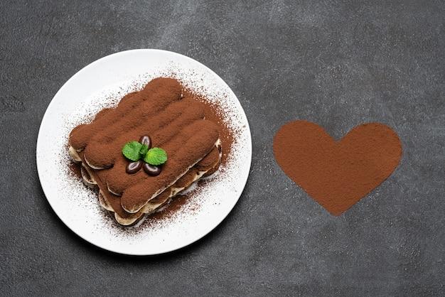 Classico dessert al tiramisù su piatto in ceramica e cacao in polvere a forma di cuore