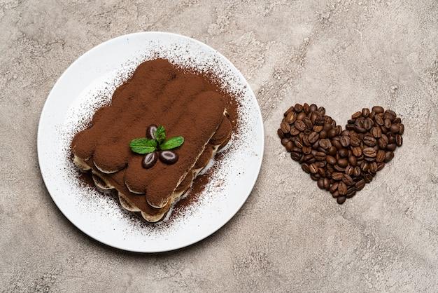 Classico dessert al tiramisù su piatto in ceramica e chicchi di caffè a forma di cuore