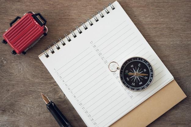 Classifiche di libri (elenco), penna e bussola per registrare vari oggetti prima di viaggiare,