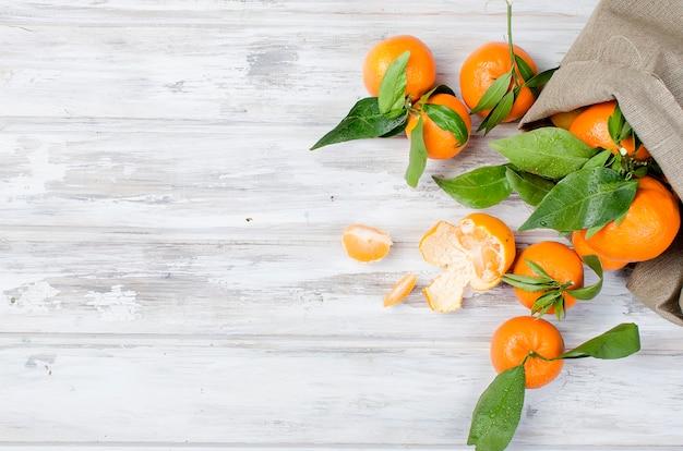 Clementine di mandarini con foglie su un tavolo di legno.