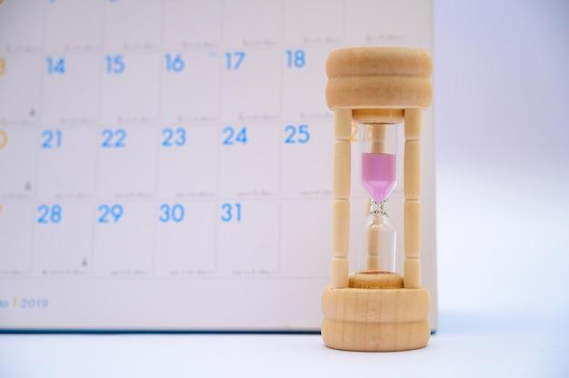 Clessidra con calendario idee giorni trascorsi tempo in ogni periodo e appuntamenti o in attesa