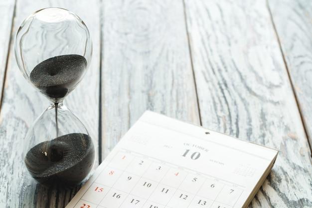Clessidra con calendario sullo scrittorio di legno. concetto di tempo