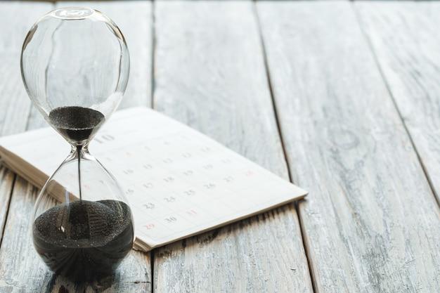Clessidra con calendario sullo scrittorio di legno