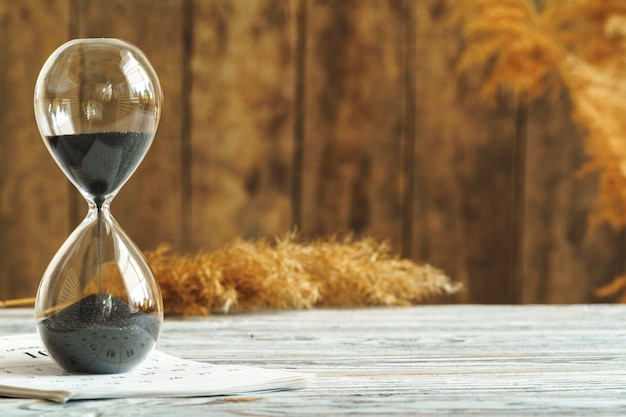 Clessidra con il calendario sulla fine di legno dello scrittorio su. concetto di tempo