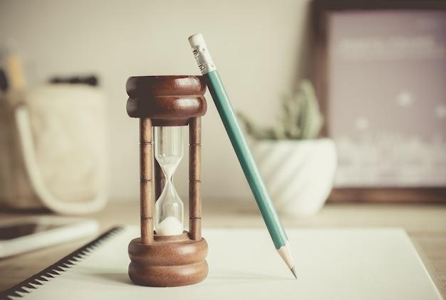 Clessidra con la matita sul taccuino, tempo che passa concetto