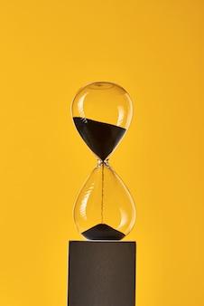 Clessidra su giallo con spazio di copia. concetto di rimanere a corto di tempo e scadenza