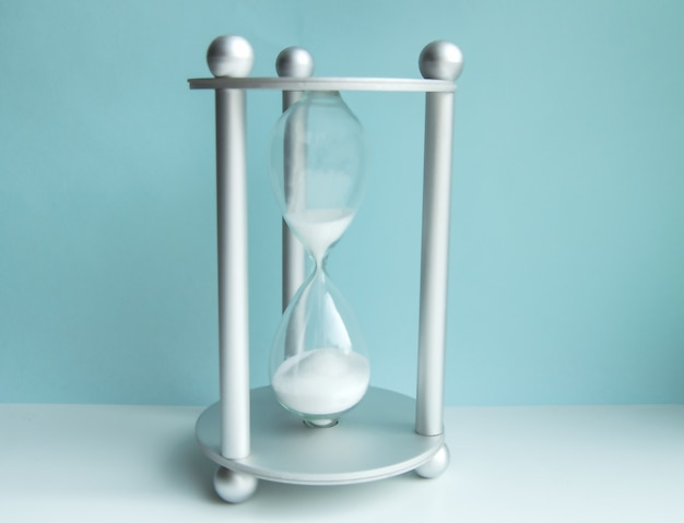 Clessidra su una parete blu. il concetto di gestione del tempo, scadenza ed equilibrio negli affari