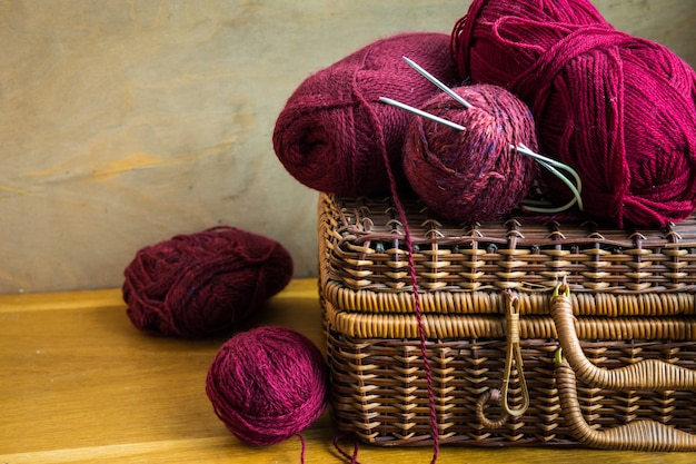 Clews di capsule di cesto di vimini d'epoca di filato di lana rosso, aghi sul tavolo di legno