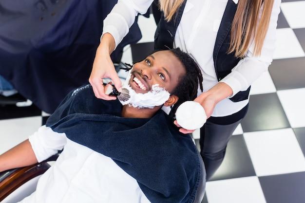 Cliente al barbiere con crema da barba