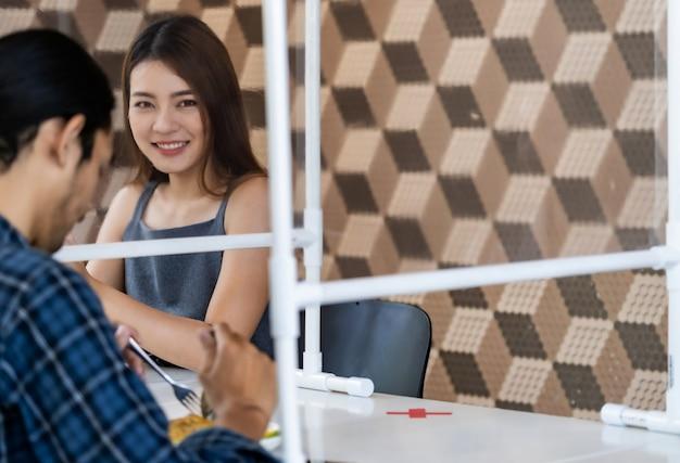 Cliente asiatico distanziante sociale in ristorante.