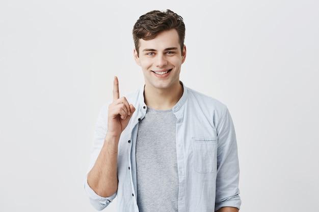 Cliente caucasico soddisfatto e soddisfatto che indica con il dito indice su nello spazio in bianco sopraelevato per la vostra pubblicità. bello uomo positivo che sorride con i denti e che gesturing, posando allo studio