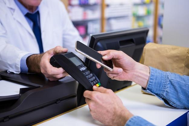 Cliente che effettua il pagamento tramite smartphone nel terminale di pagamento