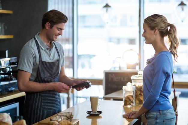 Cliente che effettua il pagamento tramite terminale di pagamento allo sportello