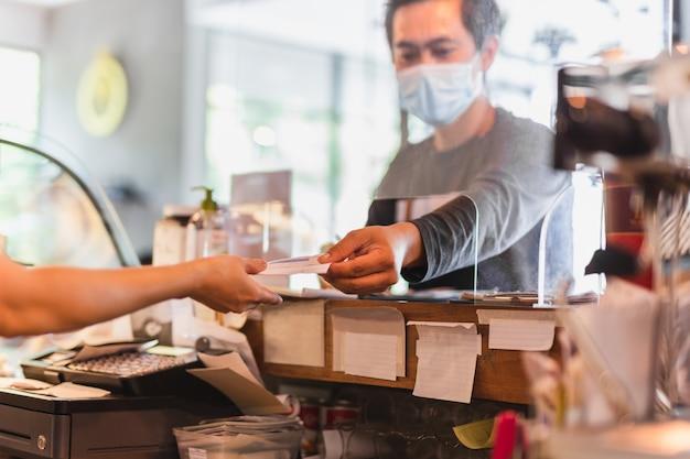 Cliente che indossa una maschera protettiva pagando la fattura al bancone con scudo divisorio.