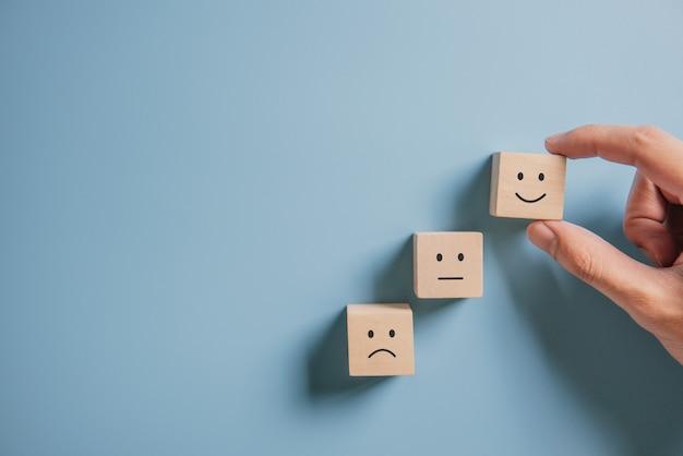 Cliente che mostra valutazione con l'icona felice sull'azzurro. concetto di indagine sulla soddisfazione del cliente