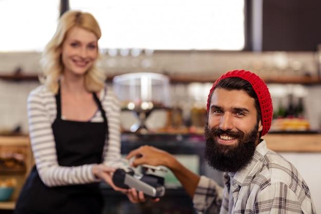 Cliente che paga dal lettore di carte bancarie con il suo smartphone