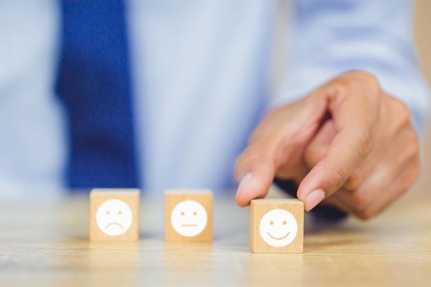 Cliente che preme emoticon del fronte di smiley sul cubo di legno