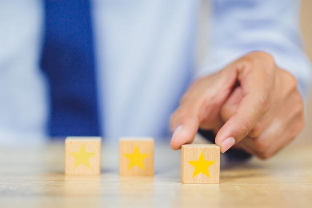 Cliente che preme stella sul cubo di legno, valutazione di servizio, concetto di soddisfazione.