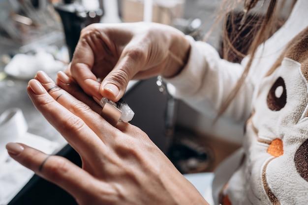 Cliente che prova le misure degli anelli a portata di mano nell'officina di gioielleria