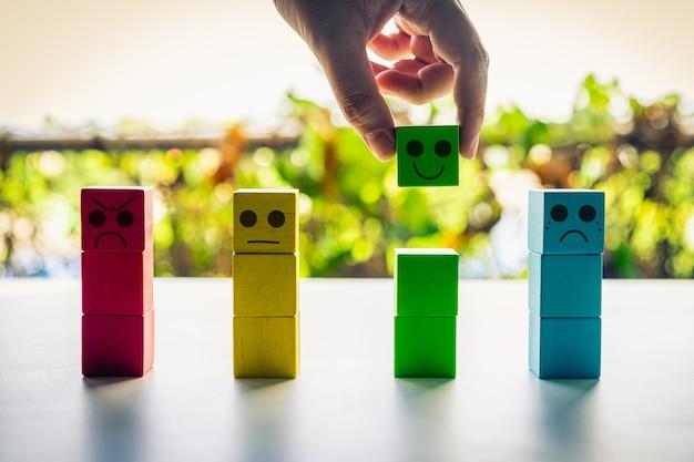 Cliente che sceglie valutazione con l'icona verde felice del blocco sulla natura